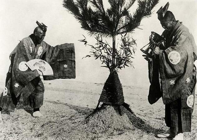 Japanese custom on New Year's Eve, monks in traditional costumes count the last seconds of the old year with an hourglass and welcome the New Year by honouring fresh green leaves on a bush. Japan, 1932. Image courtesy of Dutch National Archives