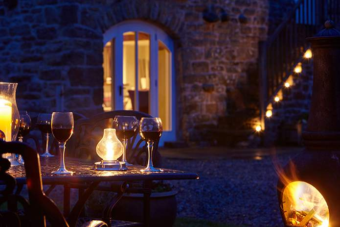 Outdoor drinks illuminated by simple candlelight at Angel Barn, A Corner of Eden, Cumbria